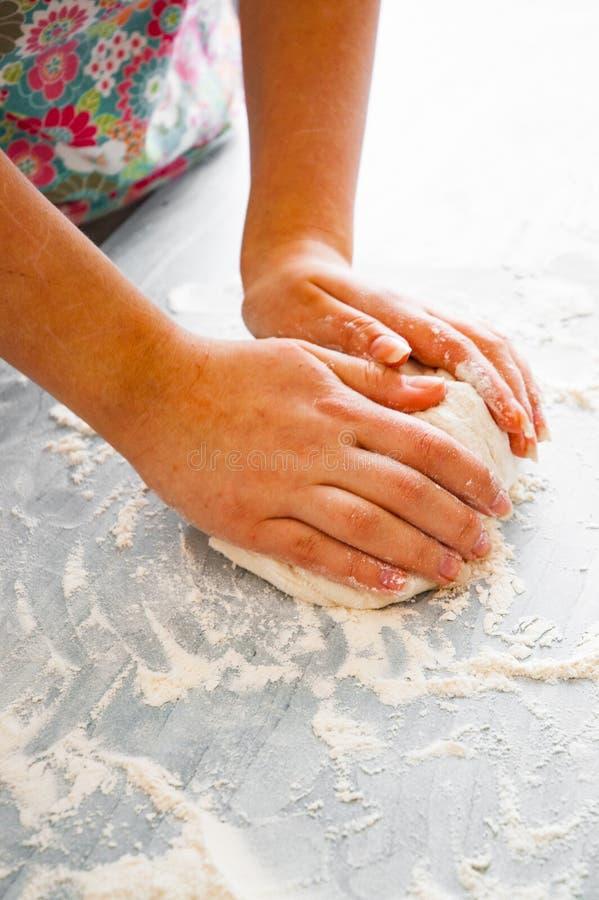 Frau ` s Hände kneten Teig auf Holztisch lizenzfreies stockfoto