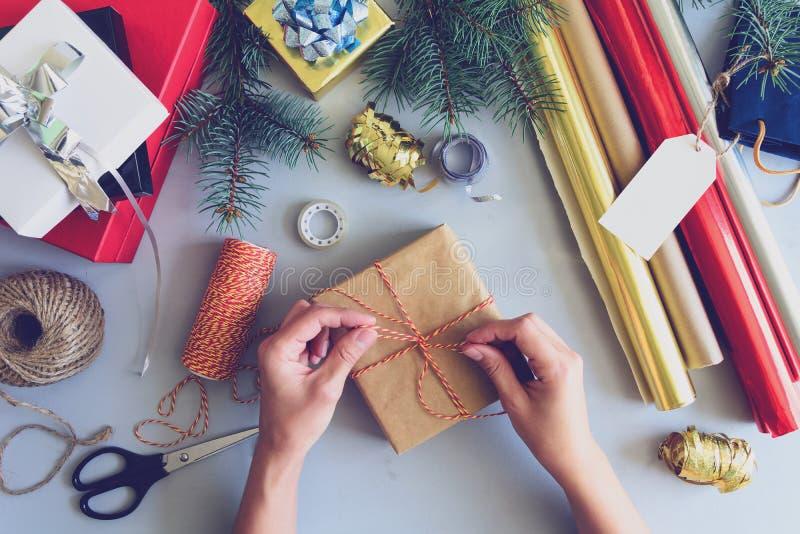 Frau ` s Hände verzieren Präsentkarton auf grauem hölzernem Hintergrund Dekorationskonzept des neuen Jahres und des Weihnachten g lizenzfreie stockfotografie
