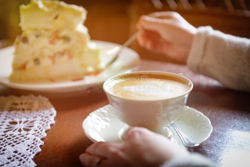 Frau ` s Hand, die Cappuccinoschale im Café hält lizenzfreie stockbilder
