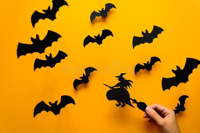 Frau ` s Hand, die Hexe auf Besen und schwarzem Papier hält, schlägt Fliegen auf gelbem Hintergrund stockbild