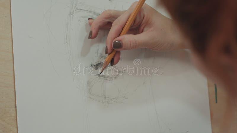 Frau ` s Hand, die klassisches Manngesicht mit Bleistift zeichnet stockbild