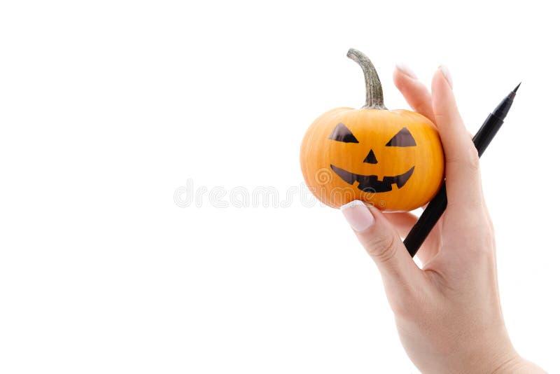 Frau ` s Hand, die kleinen Halloween-Kürbis und Markierungsstift hält lizenzfreie stockfotografie