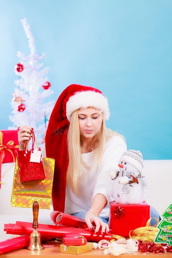 Frau in Sankt-Hut, der Weihnachtsgeschenke vorbereitet lizenzfreies stockbild