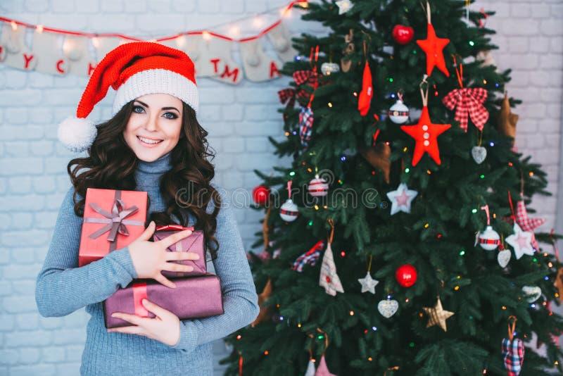 Frau in Sankt-Hut mit vielen Geschenkboxen lizenzfreies stockbild