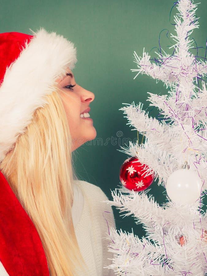 Frau in Sankt-Hut Weihnachtsbaum verzierend stockfotografie