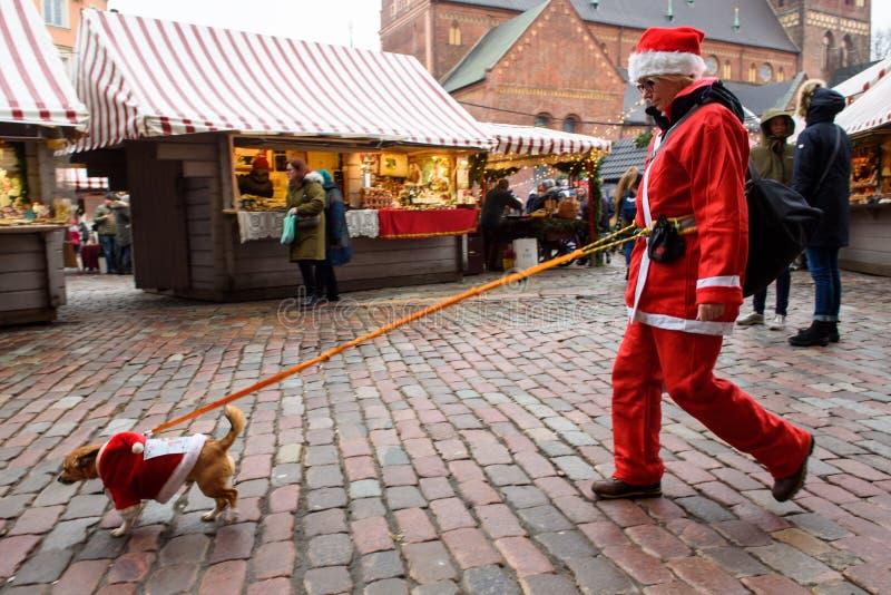 Frau in Santa Clauss-Kostüm gehend mit Hund lizenzfreie stockfotos
