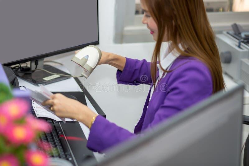 Frau scannt den Barcode auf einer Rechnung mit Lesewerkzeug lizenzfreie stockfotos