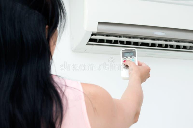 Frau schaltet Klimaanlage in einem Raum ein lizenzfreies stockfoto