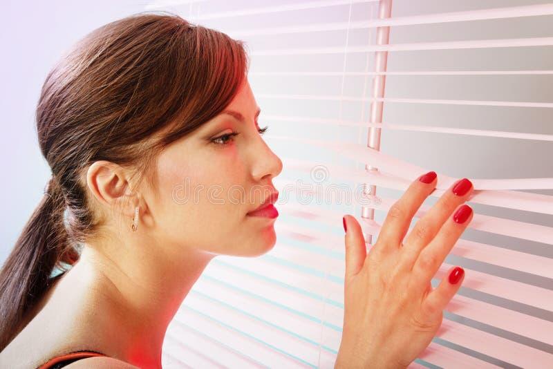 Frau schaut durch weißen Jalousie lizenzfreies stockbild