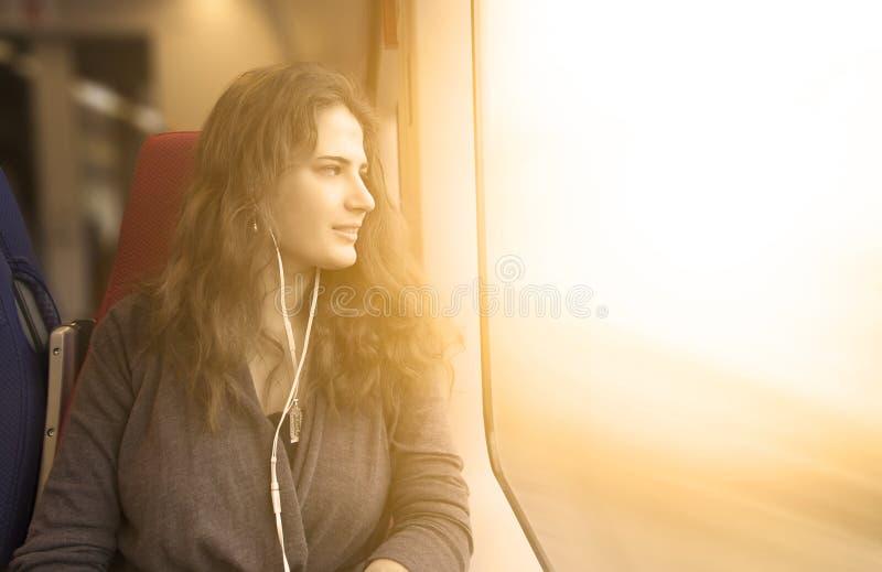 Frau schaut heraus Fenster lizenzfreies stockbild