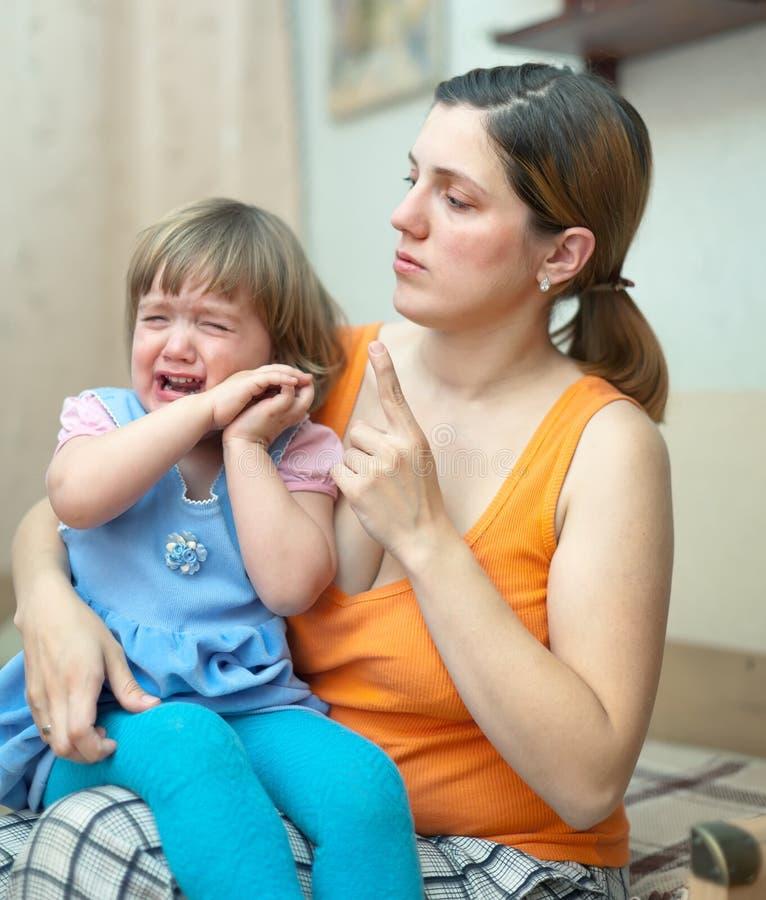 Frau schilt schreiendes Kind im Haus lizenzfreie stockfotografie