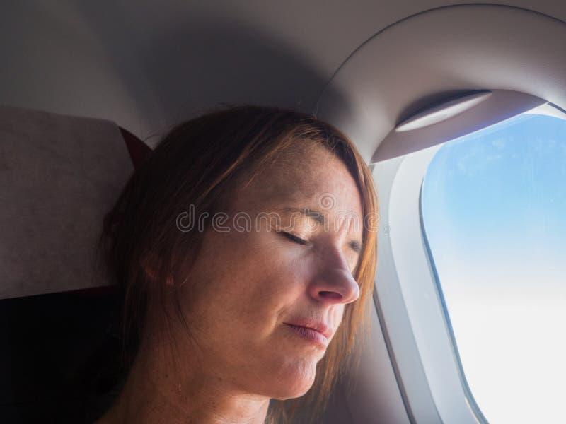 Frau schläft in den Flugzeugen lizenzfreie stockbilder