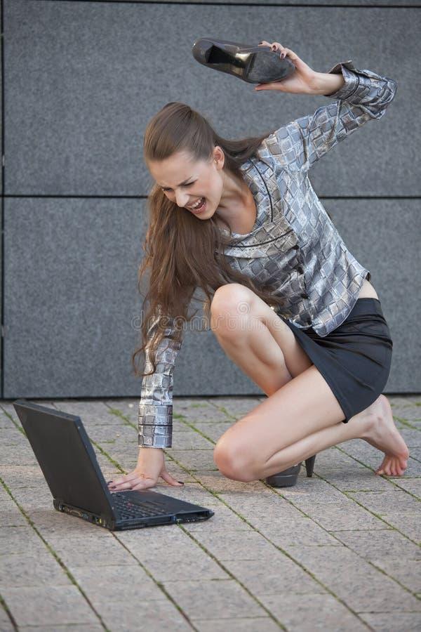 Frau schlägt Laptop mit Schuh stockbilder