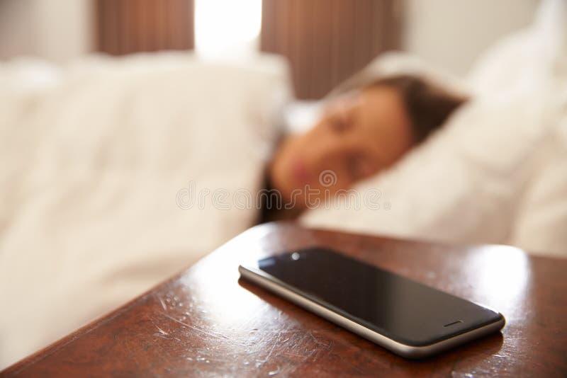 Frau schlafend im Bett mit Handy auf Nachttisch lizenzfreies stockbild