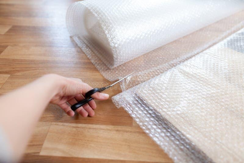 Frau schneidet Verpackungsmaterial mit scissor stockfoto