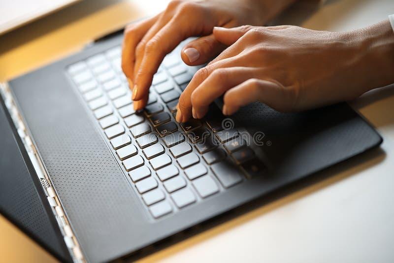 Frau schreibt auf einem Laptop stockfoto