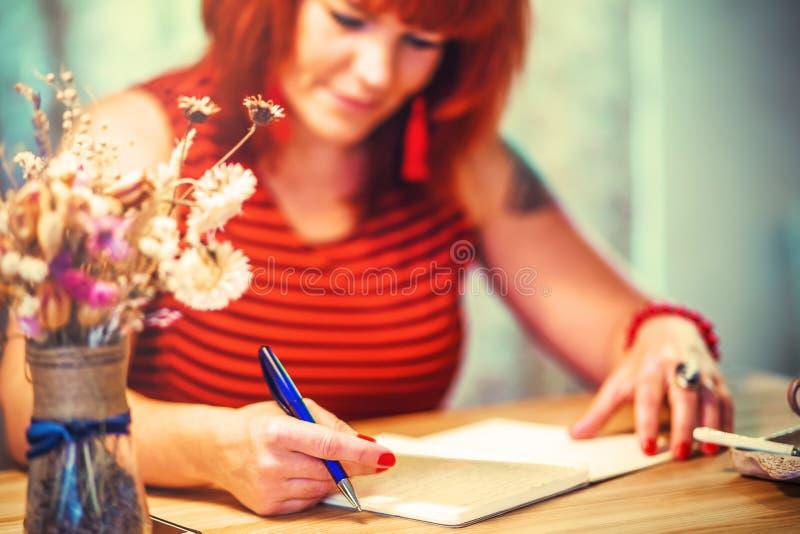 Frau schreibt in Notizblock in coofee Stange stockfotografie