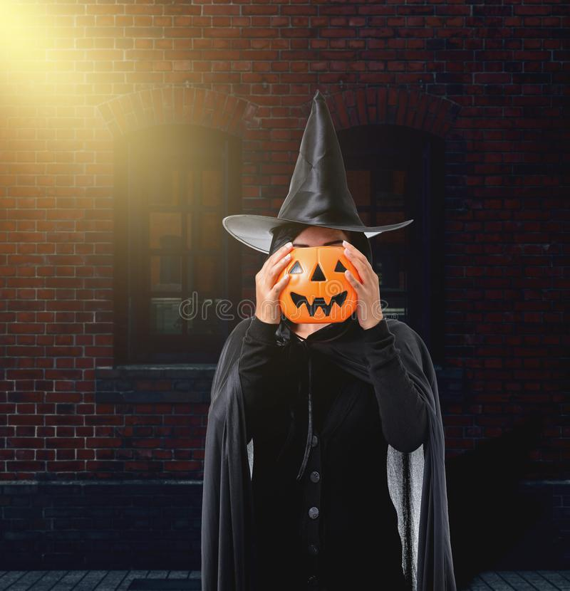 Frau in schwarzem furchtsamem Hexenhalloween-Kostüm mit Backsteinmauer von stockbilder