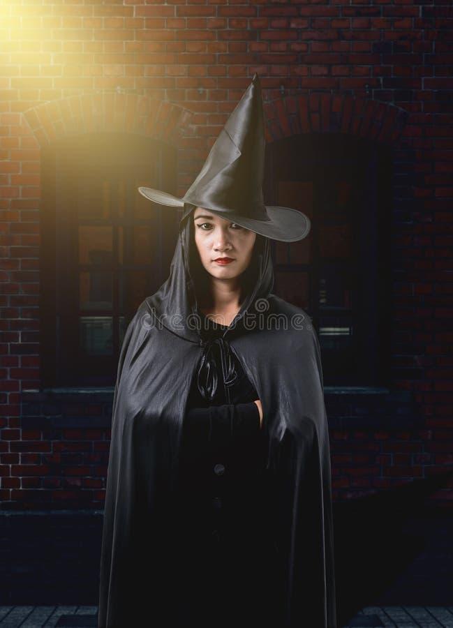 Frau in schwarzem furchtsamem Hexenhalloween-Kostüm mit Backsteinmauer von lizenzfreies stockfoto