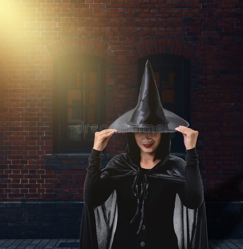 Frau in schwarzem furchtsamem Hexenhalloween-Kostüm mit Backsteinmauer von lizenzfreie stockbilder