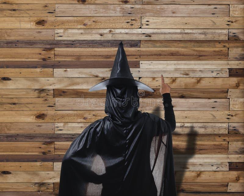Frau in schwarzem furchtsamem Hexenhalloween-Kostüm mit hölzernem Wand-PA stockfotos