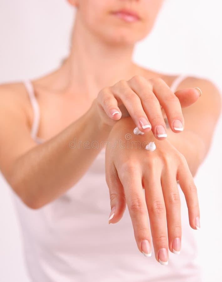 Frau setzt eine Sahne für schöne Hände stockbild