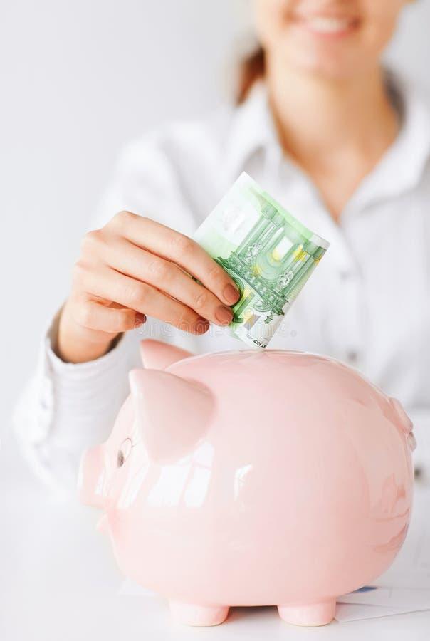 Frau setzt Eurobargeld in großes Sparschwein lizenzfreie stockfotos