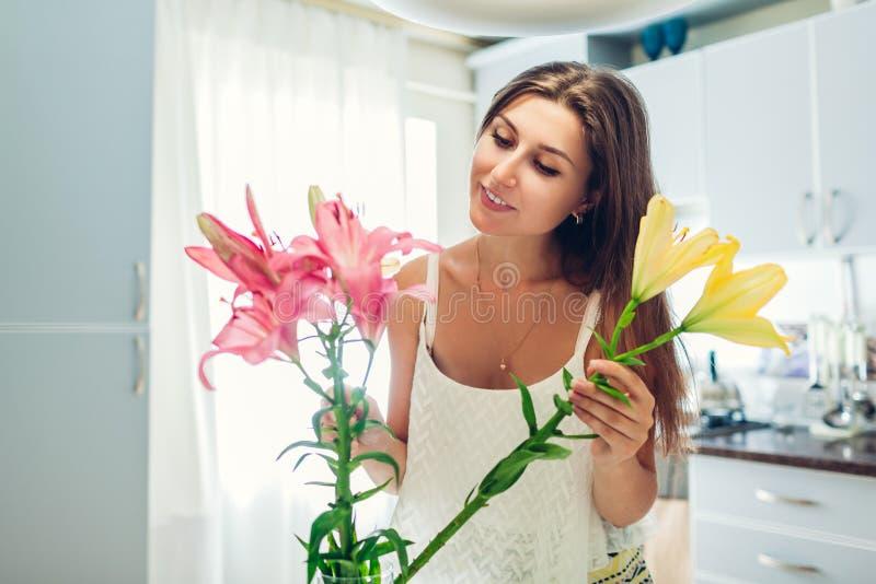 Frau setzt Lilienblumen in Vase ein Hausfrau, die um Gem?tlichkeit und Dekor auf K?che sich k?mmert Verfassender Blumenstrau? stockfotos