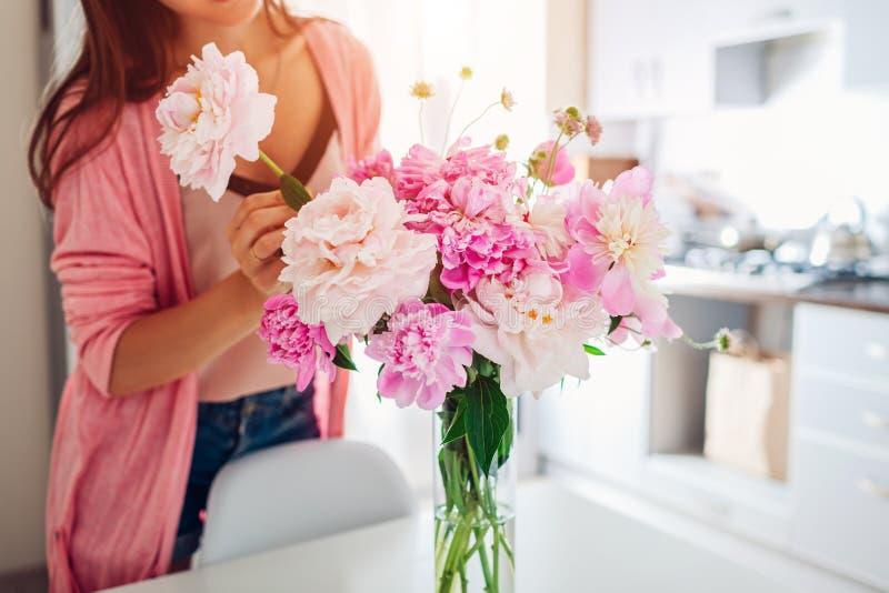 Frau setzt Pfingstrosenblumen in Vase ein Hausfrau, die um Gemütlichkeit und Dekor auf Küche sich kümmert Verfassender Blumenstra lizenzfreies stockfoto