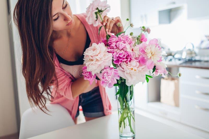 Frau setzt Pfingstrosenblumen in Vase ein Hausfrau, die um Gem?tlichkeit und Dekor auf K?che sich k?mmert Verfassender Blumenstra lizenzfreie stockbilder