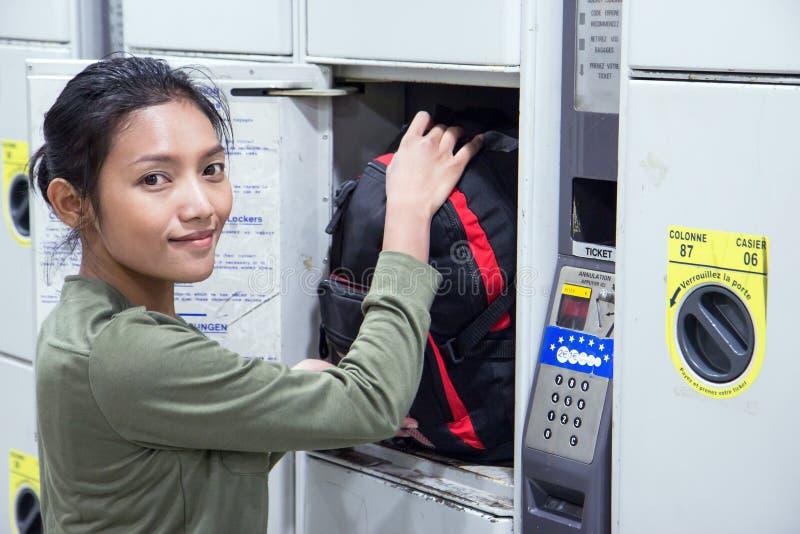 Frau setzt Rucksack zum Sicherheitsschließfach lizenzfreie stockfotos