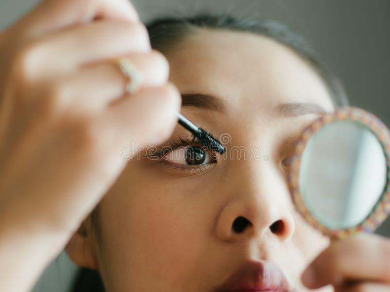 Frau setzt sich bilden Wimperntusche auf ihren Wimpern lizenzfreies stockfoto