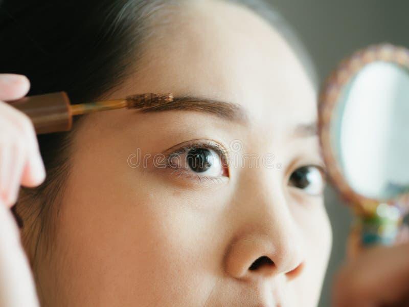 Frau setzt sich bilden Wimperntusche auf ihren Wimpern stockfotografie