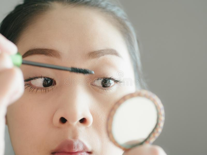 Frau setzt sich bilden Wimperntusche auf ihren Wimpern stockbild