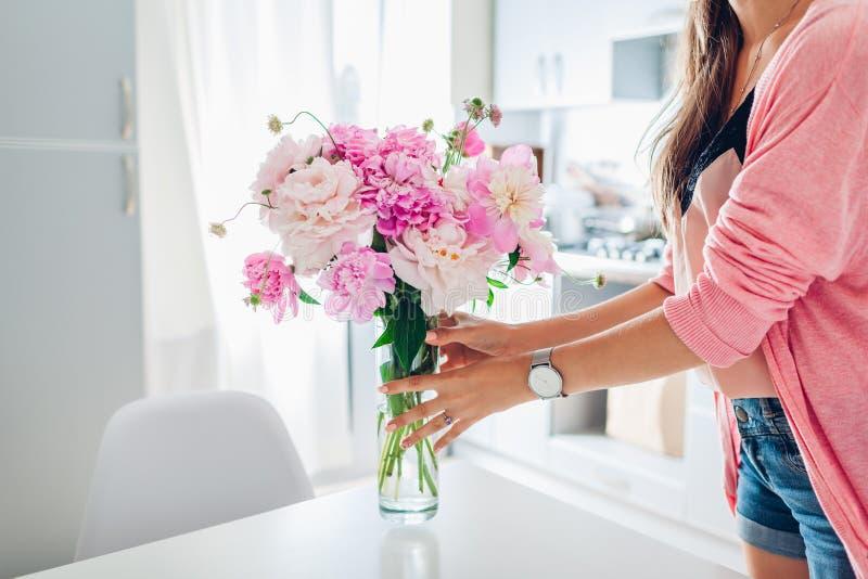 Frau setzt Vase mit Pfingstrosen Hausfrau, die um Gem?tlichkeit in der K?che sich k?mmert Moderne K?cheauslegung stockbild