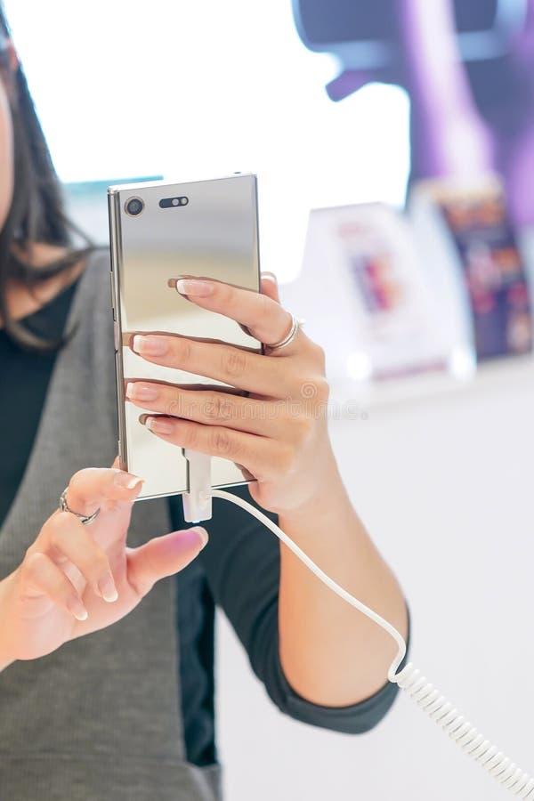 Frau sind, prüfend halten und Handy im beweglichen Geschäft lizenzfreies stockbild
