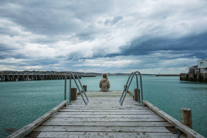 Frau sitzen am Rand der Brücke stockfotografie