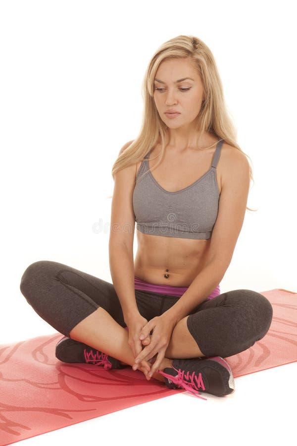 Frau sitzen rote Yogamatte lizenzfreie stockbilder
