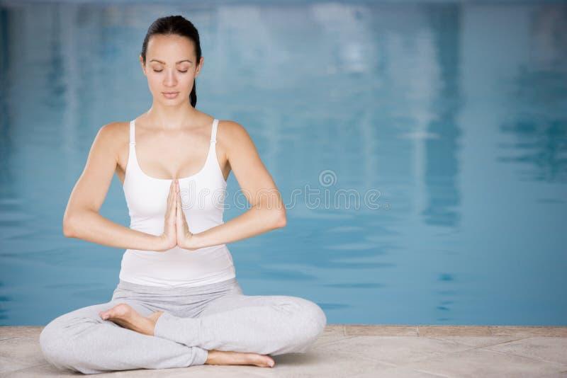 Frau sitzender Poolside, der Yoga tut stockfotos