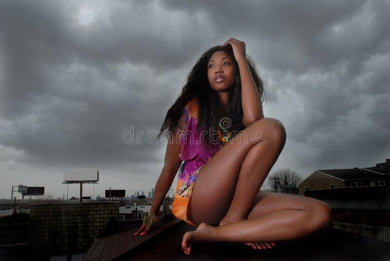 Frau sitzt auf Dachspitze lizenzfreie stockbilder