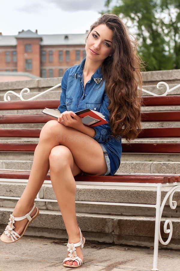 Frau sitzt auf einer Bank und liest das Buch stockbild