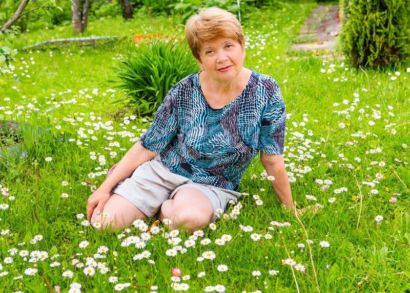 Frau sitzt auf einer Lichtung mit Gänseblümchenblumen lizenzfreies stockfoto