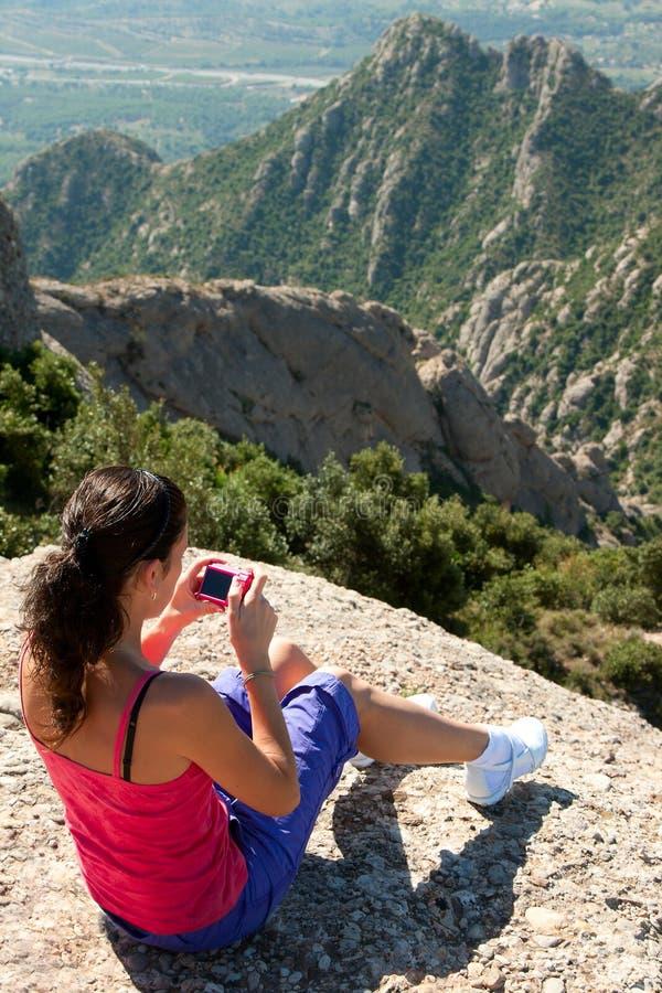 Frau sitzt auf felsigem und fotografiert stockbild