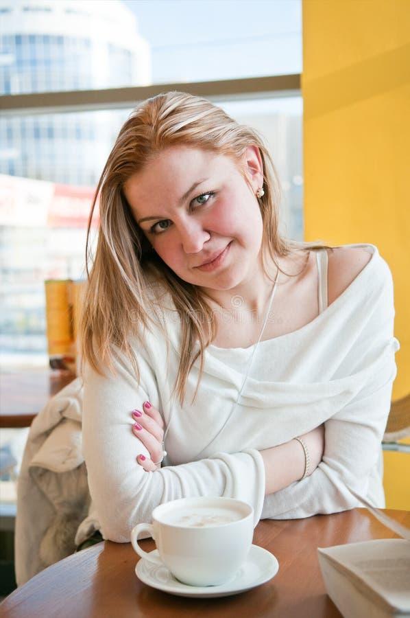 Frau sitzt am Tisch im Kaffee. Trinkt Kaffee lizenzfreies stockfoto