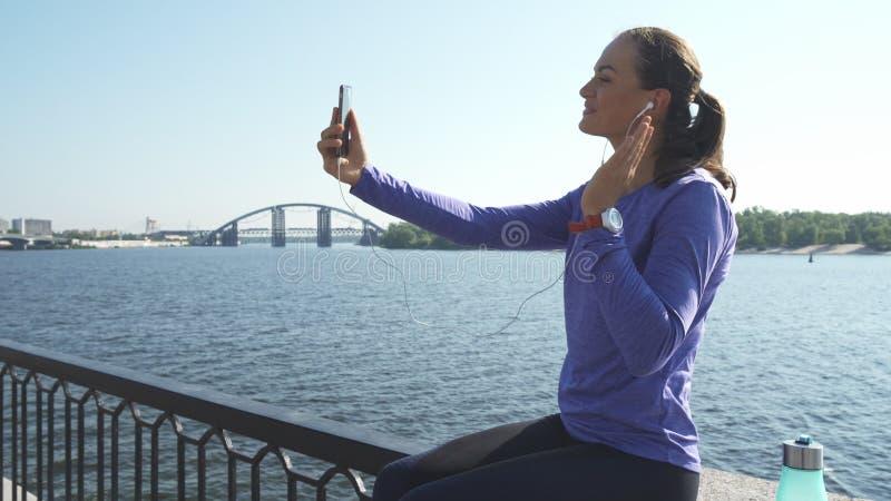Frau sitzt und Gespräch über Telefon stockfotografie