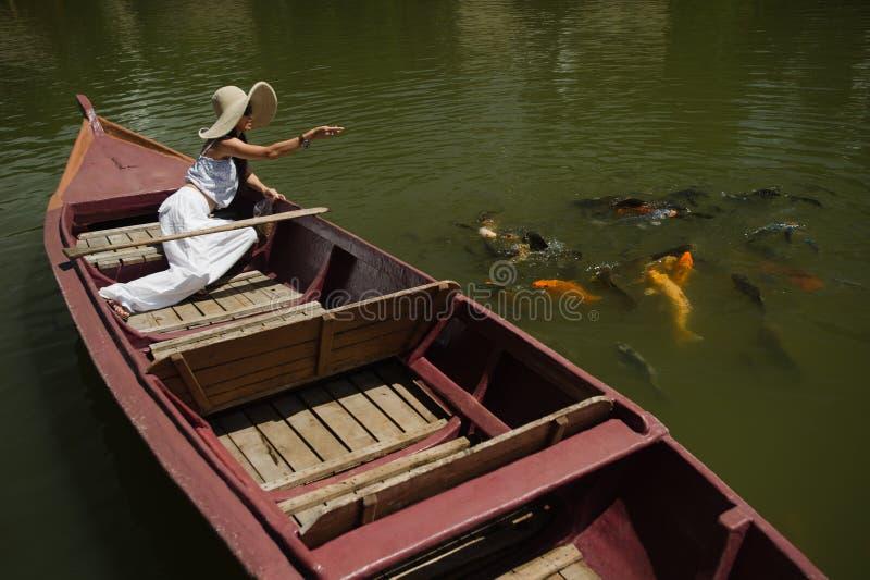 Frau speisengoldfish in einem großen Teich lizenzfreie stockfotos