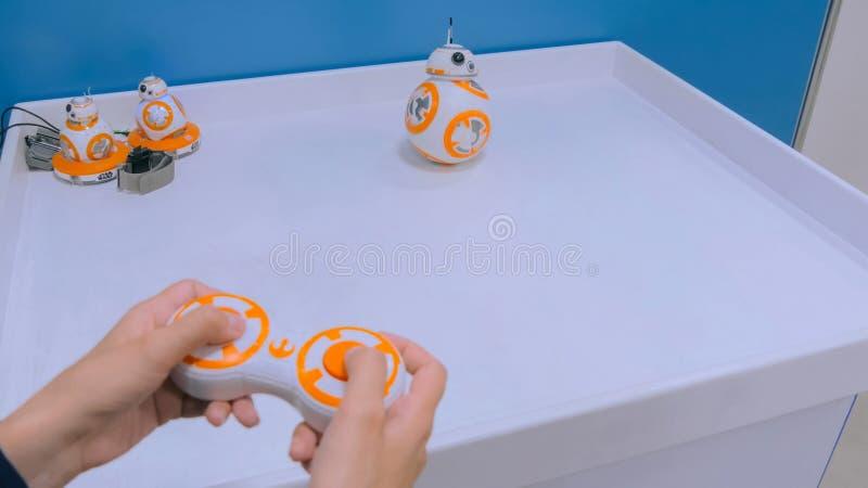 Frau spielt mit droid BB-8 von StarWars mit spezieller Fernbedienung stockbild