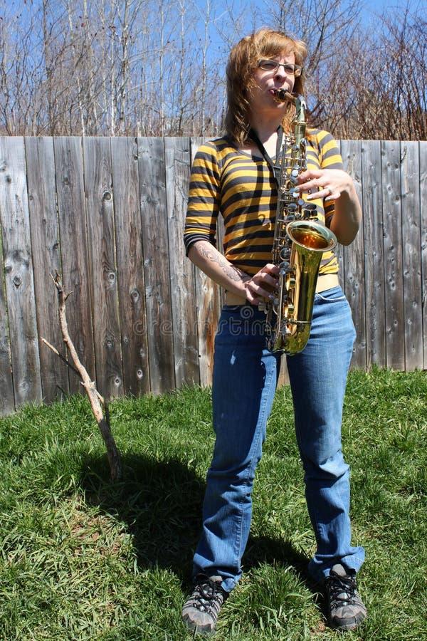 Frau spielt Saxophon draußen stockfotos