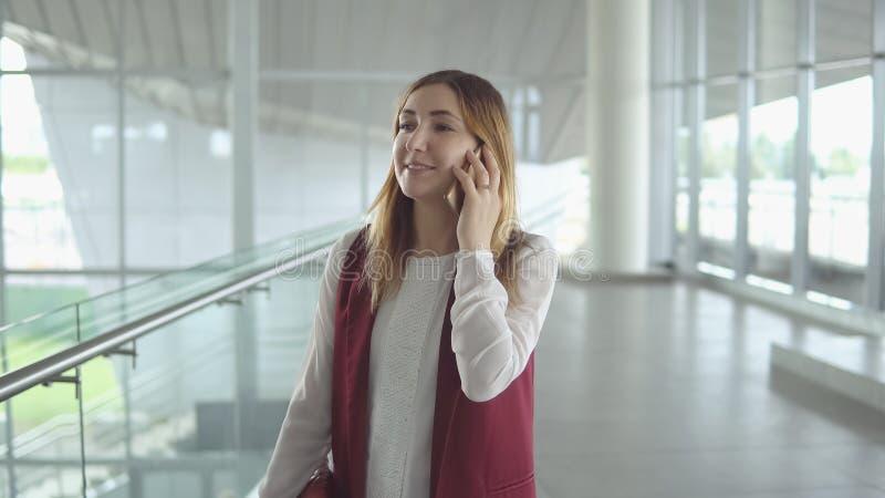 Frau spricht über Smartphone beim Besteigen auf Flugzeug lizenzfreies stockfoto