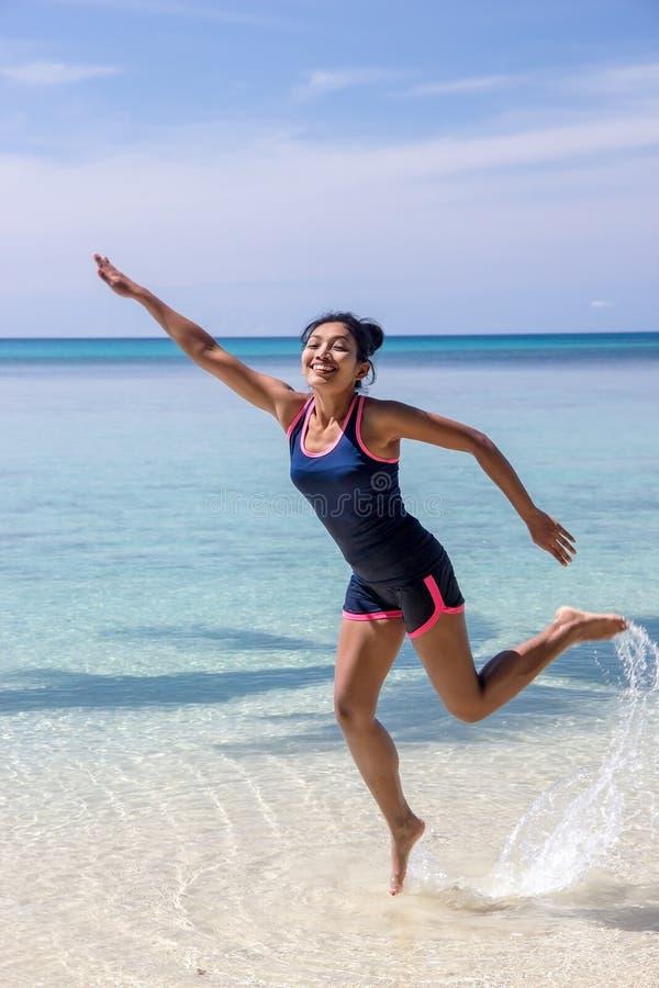 Frau springt am Meeresspiegel stockfotografie